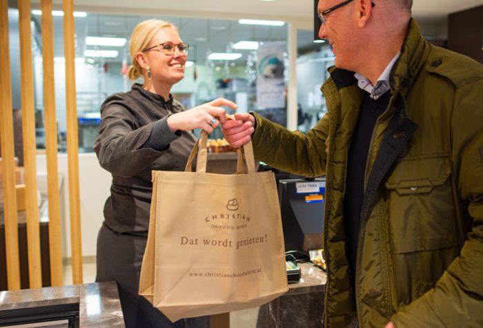 Marloes overhandigt tas aan klant